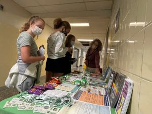 three students looking at a table filled with suicide prevention information and a health rep is explaining issues to them